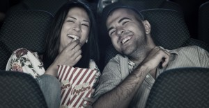 Couple watching comedy in cinema. Selected focus on girl